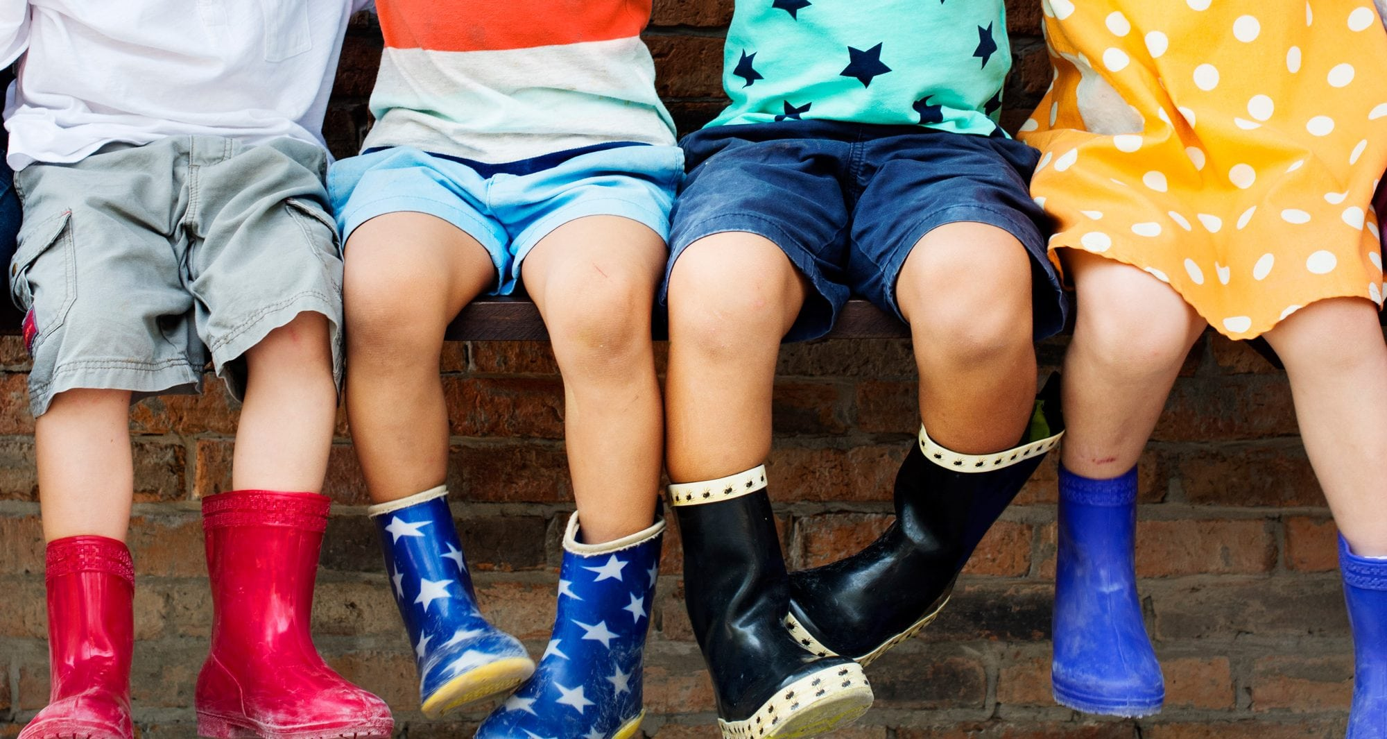 Children wearing welly boots sitting swinging legs
