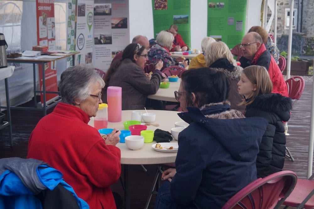 People sitting at tables eating and drinking at Bute Produce