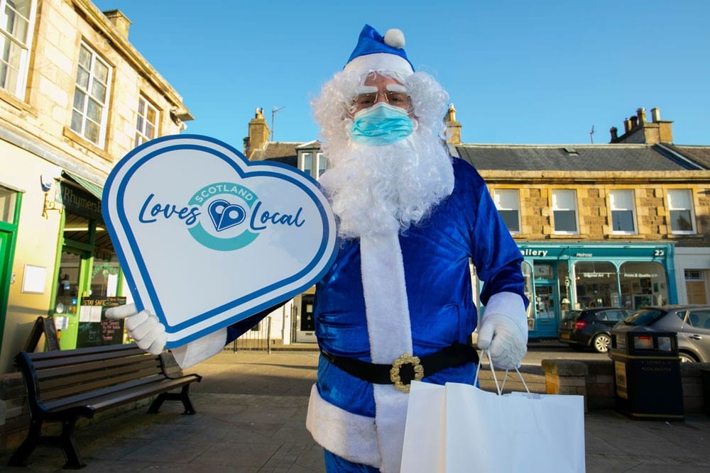 Image of a man dressed as a blue Santa Claws with a Scotland Loves Local heart shaped placard