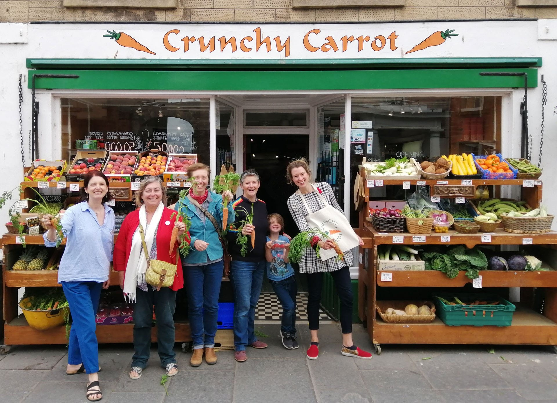 Outside view of the Crunchy Carrot on Dunbar High Street with vegetables displayed and people holding up fresh carrots