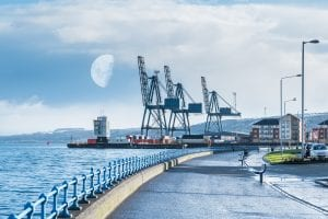 Image of Greenock's esplanade in the west end of the town looking over to the contrasting ClydePort Terminal with its port and heavy cranes in the early morning half moon and snow on the Greenock Hills