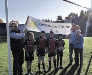 Adults holding a banner of Linlith-Go-Solar under rugby goal with children in rugby strips