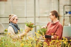Two women holding flowers, Young Enterprise Scotland, Rouken Glen Centre
